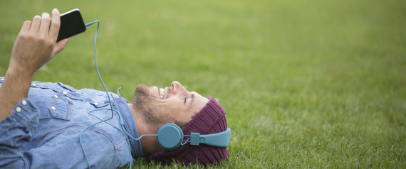 Man listening to headphones on lawn