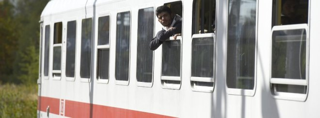 A refugee looks out a train carrying refugees to Berlin and Brandenburg at the Schoenefeld airport train station in Schoenefeld on September 28, 2015. The refugees are transported with a special train from Salzburg as the train service between Austria and Germany is interrupted until October 4, 2015. AFP PHOTO / TOBIAS SCHWARZ