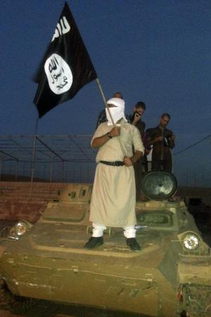 A-fighter-of-the-ISIL-holds-a-flag-while-standing-on-an-armoured-vehicle-in-Mosu
